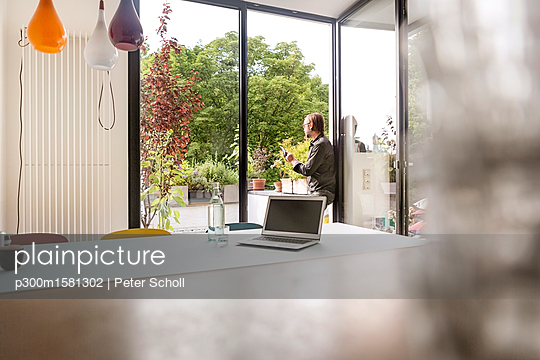 Germany, businessman using tablet on balcony, laptop on table - p300m1581302 von Peter Scholl