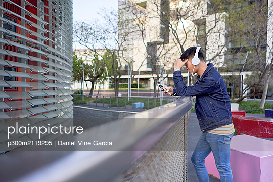Young man with headphones looking at cell phone, Barcelona, Spain - p300m2119295 by Daniel Vine Garcia