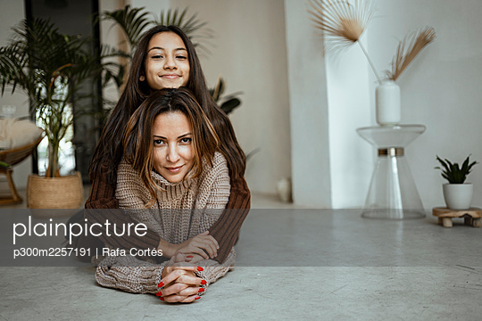 Smiling daughter with arms around of mother while lying on floor at home - p300m2257191 by Rafa Cortés
