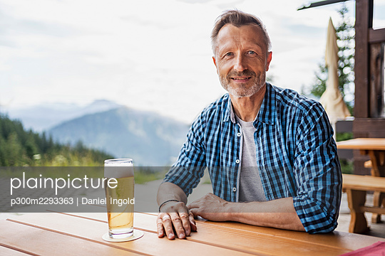 Smiling man sitting with beer glass at bar table - p300m2293363 by Daniel Ingold