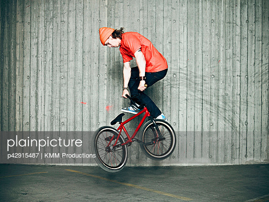 Man doing tricks on bmx bike indoors