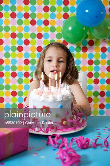 Girl sitting in front of a birthday cake - p5530102 by Christine Basler