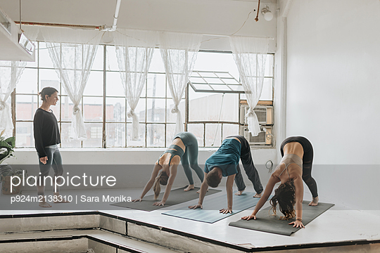Yoga instructor teaching yoga in studio - p924m2138310 by Sara Monika