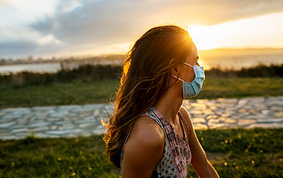 Young woman in protective face mask against sky during COVID-19 outbreak - p300m2221412 by Marco Govel