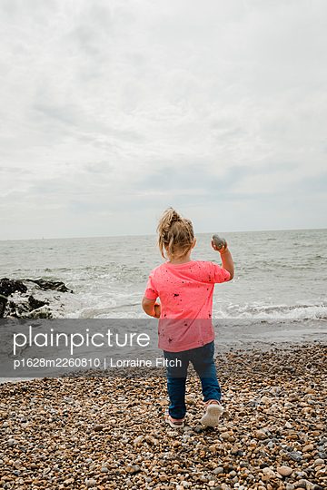 Little girl throwing a stone into the sea - p1628m2260810 by Lorraine Fitch