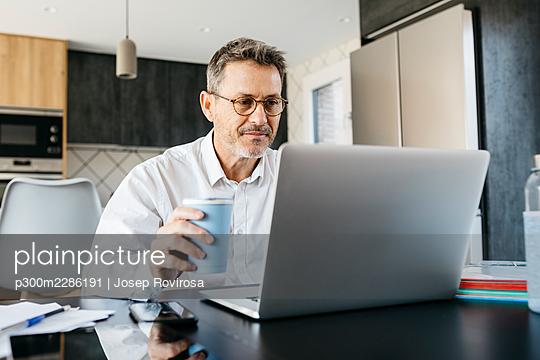 50-year-old man working at home, dining room and kitchen - p300m2286191 von Josep Rovirosa