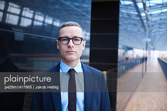 Portrait of confident businessman on office balcony - p429m1417965 by Jakob Helbig