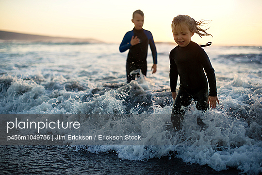 Two young children playing in the surf at sunset - p456m1049786 by Jim Erickson / Erickson Stock