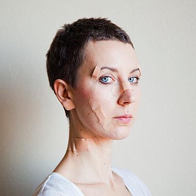 Junge Frau mit Pflastern im Gesicht - p1008m1169089 von Valerie Schmidt