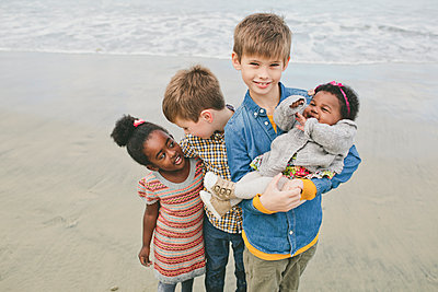Portrait of smiling boy standing with siblings at beach - p1166m1473695 by Cavan Images