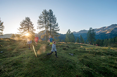Family hiking in alpine meadow at sunset - p300m1588053 by Hans Huber