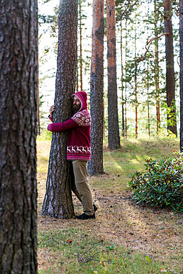 Finland, Young man hugging trees in a forest - p300m2042258 by Kike Arnaiz