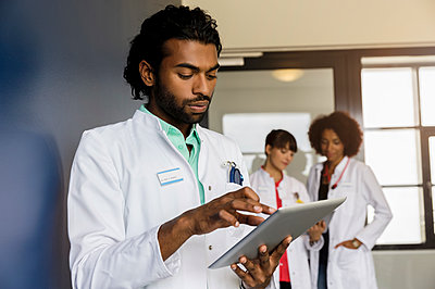 Young male healthcare worker using digital tablet with female colleagues standing in background at hospital - p300m2281535 by Buero Monaco