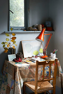 Desk and chair with patchwork tablecloth below window in Isle of Wight home;  UK - p349m920028 by Rachel Whiting