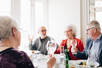 Senior friends with wineglass toasting in restaurant - p426m2149139 by Maskot
