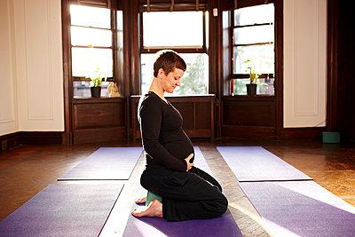 Pregnant woman sitting on yoga mat - p555m1463655 by Granger Wootz