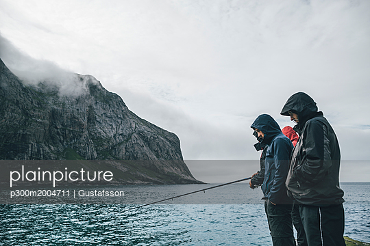 Norway, Lofoten, Moskenesoy, Young men fishing at Horseid Beach - p300m2004711 von Gustafsson