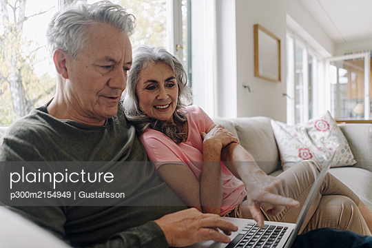 Happy senior couple with laptop relaxing on couch at home - p300m2154949 by Gustafsson