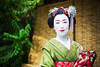 A woman dressed in the traditional geisha style, wearing a kimono and obi, with an elaborate hairstyle and floral hair clips, with white face makeup with bright red lips and dark eyes.  - p1100m1185720 by Mint Images