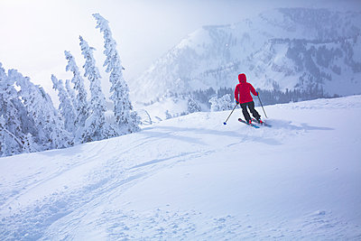 Rear view of woman skiing on snow covered landscape - p1166m1210861 by Cavan Images