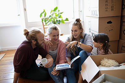 Multi-generation family reading book, taking a break from moving - p1192m2016812 by Hero Images