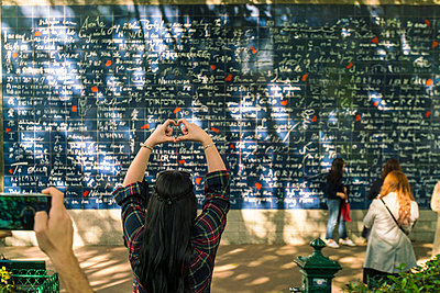 The wall of I love you with tourist making heart shape with her hand infront of it - p1332m1502802 by Tamboly