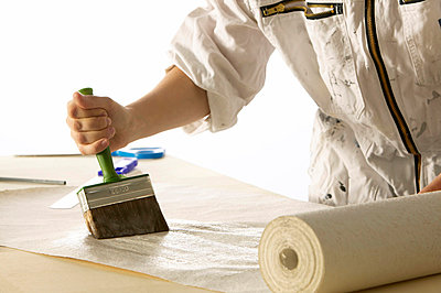 Woman pastes wallpaper - p3003817f by Tom Hoenig