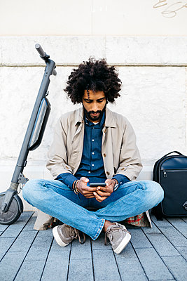 Man sitting on his E-Scooter using mobile phone - p300m2114503 by Josep Rovirosa