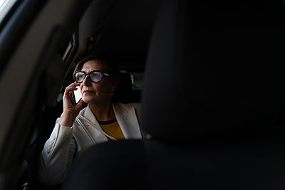 Senior businesswoman sitting in a cab, using smartphone - p300m2166939 by Eloisa Ramos