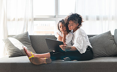 Mother and daughter sitting together on sofa with digital tablet - p300m2242704 by Josu Acosta