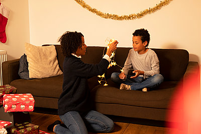 Mother and son with Christmas lights in living room at home - p300m2243274 by Pete Muller