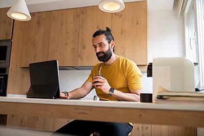 Mature man using tablet PC at home - p300m2281981 by Jose Carlos Ichiro