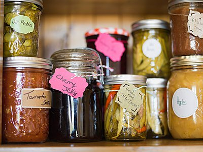 Fresh jam, pickled vegetables and canned fruits on shelf - p328m906627f by Hero Images