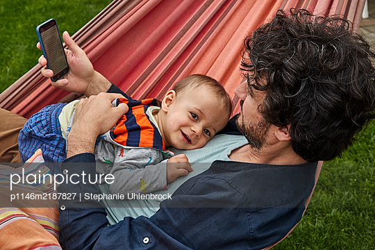 Father with son in the hammock, portrait - p1146m2187827 by Stephanie Uhlenbrock
