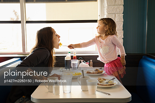 Toddler daughter feeding mother in diner - p1427m2283150 by Roberto Westbrook