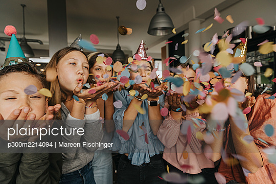 Playful friends blowing confetti while enjoying birthday party at home - p300m2214094 by Mareen Fischinger