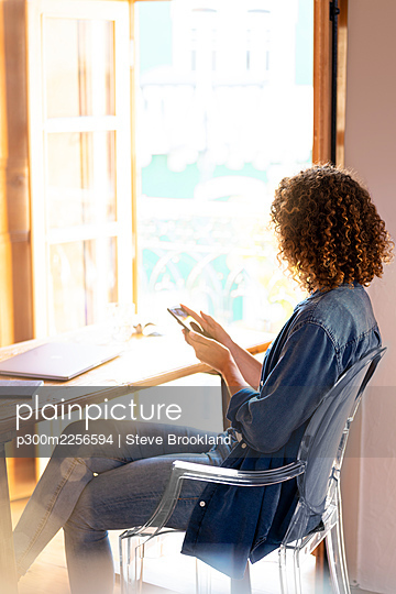 Female entrepreneur with mobile phone sitting on chair at home - p300m2256594 by Steve Brookland