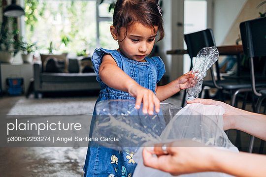 Girl helping daughter collecting crushed plastic bottle in garbage bag at home - p300m2293274 by Angel Santana Garcia