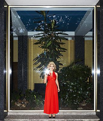 Blonde Frau in einem roten Abendkleid - p1081m2232103 von Cédric Roulliat