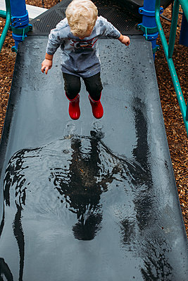 Toddler boy skipping in the playground - p1238m1462495 by Amanda Voelker