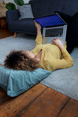 Young woman lying on the floor at home using laptop - p300m1535825 by harry + lidy