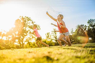 Girls blowing bubbles in grass field - p555m1411520 by John Fedele
