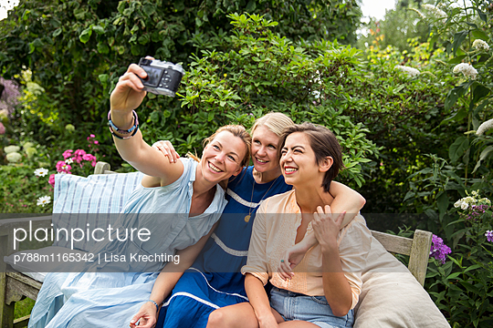 Freundinnen machen ein Selfie auf der Gartenbank - p788m1165342 von Lisa Krechting