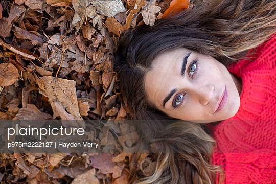 Young woman in red jumper on autumn leaves - p975m2222127 by Hayden Verry