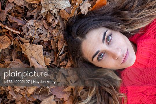 Junger Frau im roten Pullover auf Herbstblättern - p975m2222127 von Hayden Verry