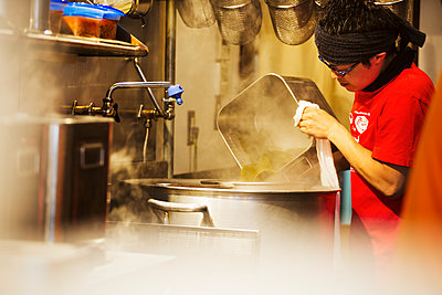 The ramen noodle shop. A chef working in a kitchen preparing food using a stove and large pans.   - p1100m1185667 by Mint Images