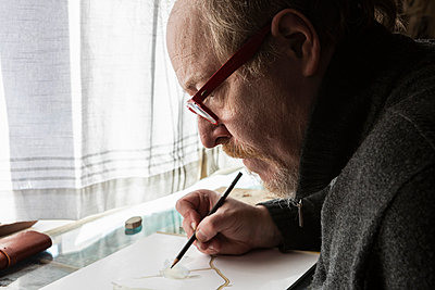 Mature artist at work drawing on paper, a wildlife study of birds.   - p1100m2249059 by Mint Images