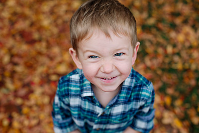 High angle portrait of cute smiling boy standing in park during autumn - p1166m2068119 by Cavan Images