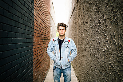 Portrait confident young man standing in alley - p1192m2110044 by Hero Images