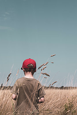 Anonymous boy standing in a field - p1228m2116344 by Benjamin Harte